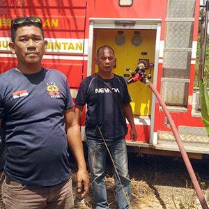 Tim Kantor UPT Damkar Toapaya tengah memadamkan api yang membakar hutan di KM 17, Jalan Lintas Barat, Kabupaten Bintan